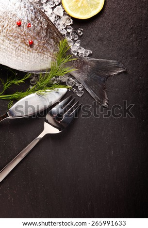 Fresh sea bream fish lying cooling on crushed ice with herbs and spices for cooking and a fish knife and fork arranged on the corner over slate with copyspace - stock photo