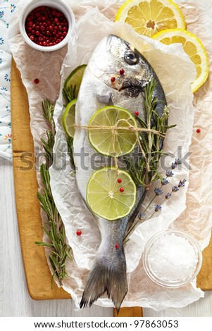Fresh sea bream with lemon, lime, rosemary, salt and pink pepper on wooden cutting board and paper wrapping - stock photo