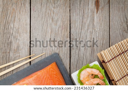 Fresh sea food and kitchen utensils on wooden table with copy space - stock photo