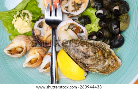 Fresh seafood at seaside cafe in Brittany, France. Selective focus on closed oyster at the right lower corner. - stock photo