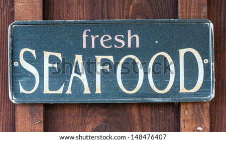 Fresh Seafood restaurant sign on wooden wall - stock photo