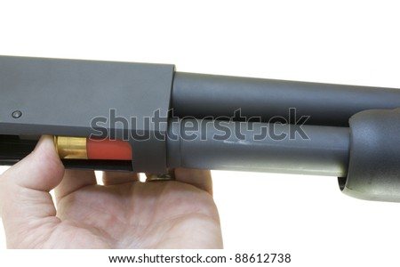 Fresh shotshell being instered into a pump action shotgun - stock photo