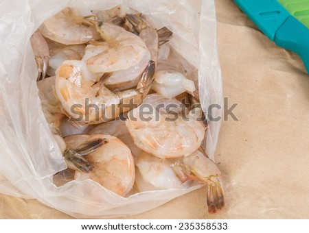 Fresh shrimp pouring from plastic bag onto cutting board in preparation for grilling. - stock photo
