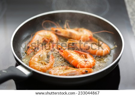Fresh shrimps being fried in olive oil - very shallow DOF - stock photo
