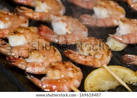 Fresh skewered Prawns in a Skillet (close-up shot) - stock photo