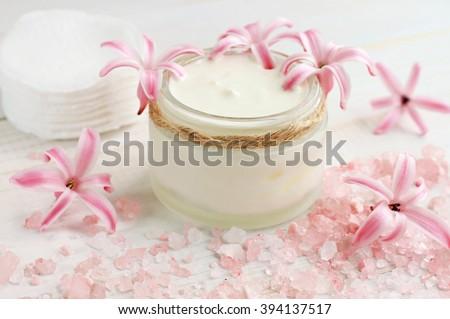 Fresh skin care cream, flowers, pink bath salt, cotton pads. Natural beauty treatment. - stock photo