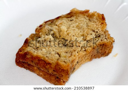 fresh slice of banana bread isolated on white plate - stock photo