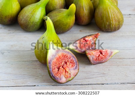 Fresh sliced and whole green figs on a wooden table. - stock photo