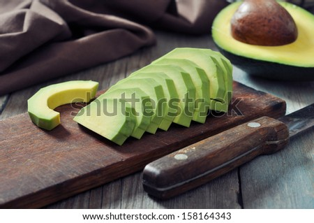 Fresh sliced avocado on cutting board over wooden background - stock photo