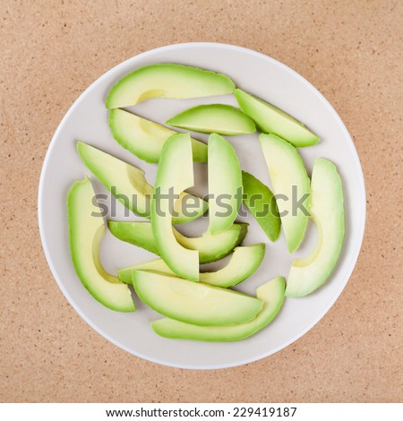 Fresh sliced avocado on plate, over wooden background. - stock photo