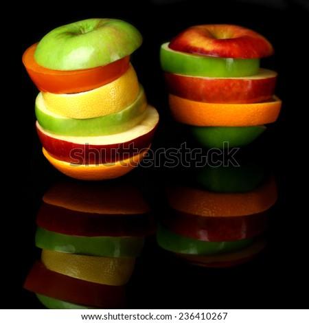 Fresh sliced fruit isolated on black - stock photo