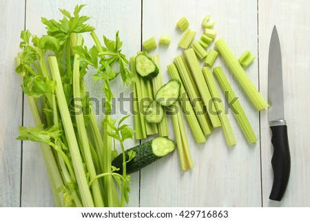 Fresh sliced green celery with cucumber near a knife on white wooden background - stock photo