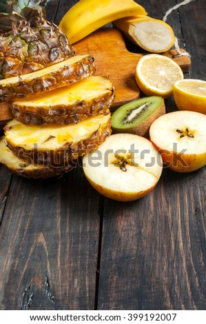 Fresh sliced pineapple and fruits on a wood table. Top view - stock photo