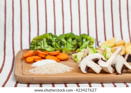 Fresh sliced soup ingredients on wooden cutting board. Side view, low aperture shot - stock photo