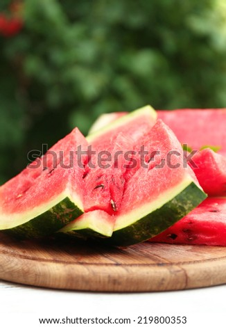 Fresh slices of watermelon on table, outdoors - stock photo