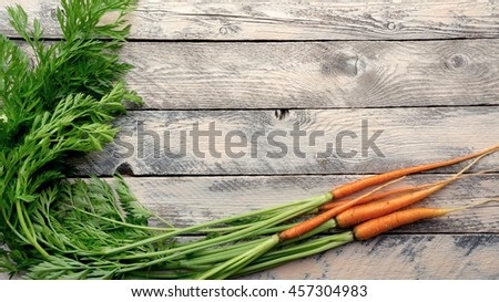 Fresh small orange carrots with leaves on wooden background. Top view - stock photo