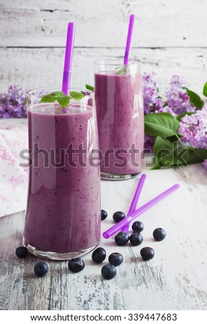fresh smoothie with blueberries in a glass on a white wooden background. ripe blueberries. health and diet  beverage. selective focus - stock photo