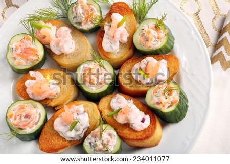 Fresh snack with salmon and shrimp on a plate - stock photo