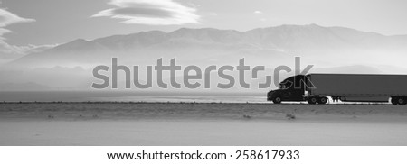 Fresh snow covers the ground trucks pass late in the day on this lonely highway - stock photo