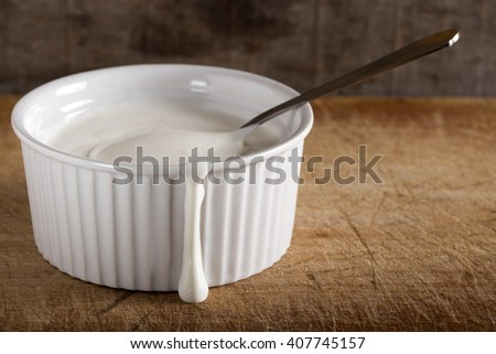 Fresh sour cream in white bowl with spoon over wooden background - stock photo