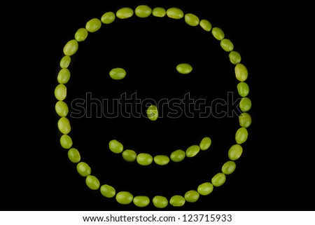 Fresh soybeans forming a smiley face on a black background - stock photo