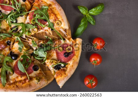 Fresh spicy italian pizza with salami sausage and fresh rocket - stock photo
