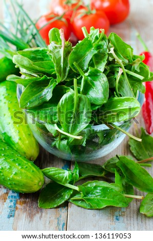 Fresh spinach , cucumbers and tomatoes on a wooden table, selective focus - stock photo