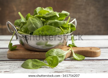 Fresh spinach in bowl - stock photo