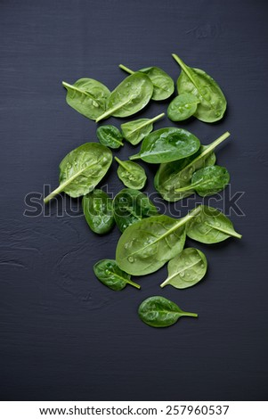 Fresh spinach leaves over black wooden surface, above view - stock photo