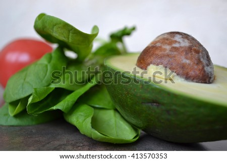 Fresh spinach, tomato and avocado. Close up of the vegetables. Dark background. Stone kitchen counter. Ripe halves of avocado. Bright  red and green. - stock photo