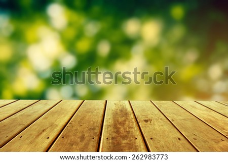 fresh spring green garden with green bokeh and sunlight over wood floor. beauty natural background - stock photo