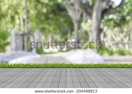 Fresh spring green grass on white and mortar wall - stock photo