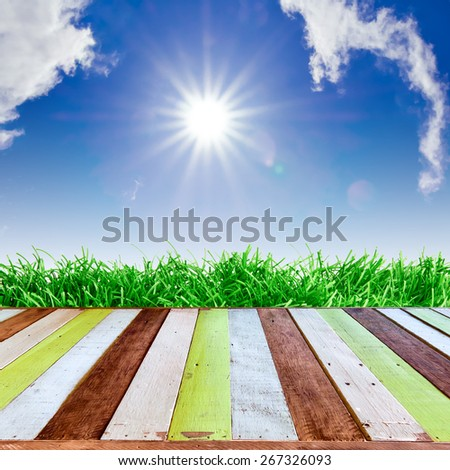 Fresh spring green grass with blue sky and  sun ray on wood floor. Natural background - stock photo