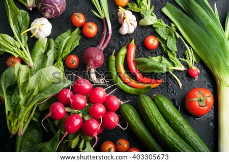 Fresh spring juicy vegetables such as radishes, tomatoes, hot peppers, cucumbers and spinach leaves on a blackboard. Vegetarian concept.  - stock photo