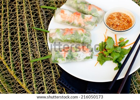 Fresh spring rolls with rice noodles, pork, prawn and herbs with peanut chili sauce on a white plate, - stock photo