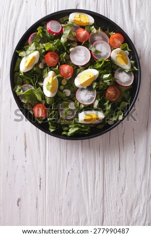 Fresh spring salad with eggs, tomato, radish and herbs on a plate. vertical top view - stock photo