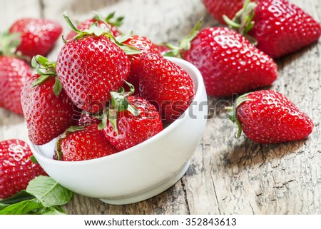 Fresh spring strawberries in a bowl, selective focus - stock photo