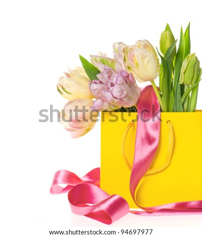 fresh spring tulips in yellow bag over white background - stock photo