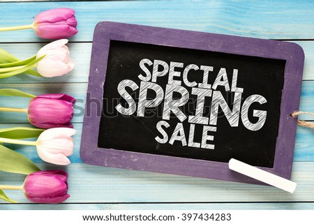 Fresh spring tulips with blackboard and text special spring sale on blue wooden background - stock photo