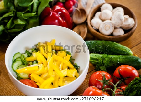 Fresh spring vegetables on the kitchen table. Homemade food preparation. - stock photo