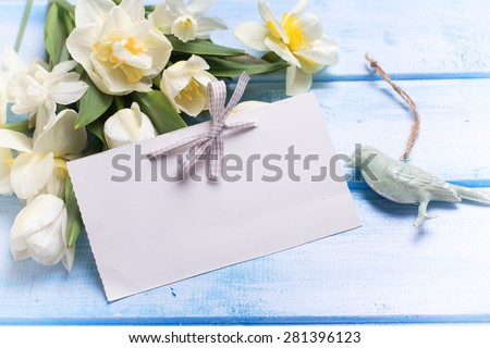 Fresh  spring white tulips and narcissus flowers and empty tag   on blue  painted wooden background. Selective focus is on tag. Place for text.  Toned image. - stock photo