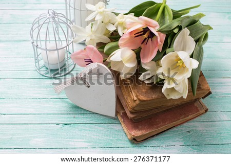 Fresh  spring yellow tulips and narcissus flowers on old books, decorative heart, candles in bird cages on turquoise  painted wooden background. Selective focus. - stock photo