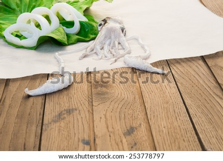 Fresh squid on wooden table, close-up on tentacles, shallow depth of field. On background green lettuce and cutted squid - stock photo