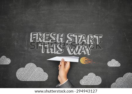 Fresh start this way concept on black blackboard with businessman hand holding paper plane - stock photo
