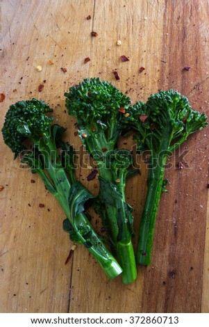 fresh steamed broccolini seasoned with sea salt and pepper flakes served on a wooden table - stock photo