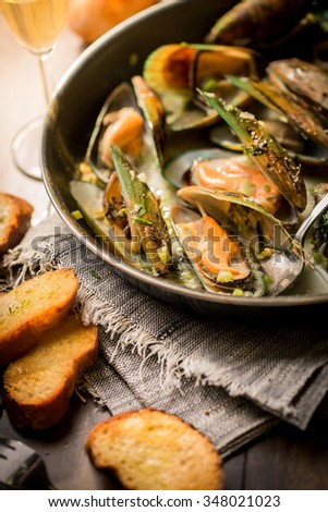 Fresh Steamed Mussels in White Wine Sauce on a wooden board. - stock photo