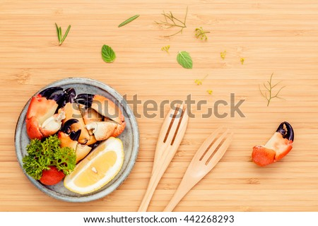 Fresh steamed red crabs leg in bowl . Red crabs leg with ingredients. Steamed red crabs leg with herbs Fennel ,parsley,rosemary,lemon and mint with fork on wooded cutting board. - stock photo
