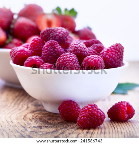 fresh strawberries and raspberries in white cup on wooden table - stock photo