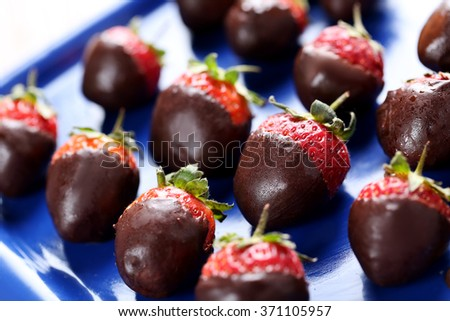 Fresh strawberries dipped in dark chocolate on blue tray - stock photo