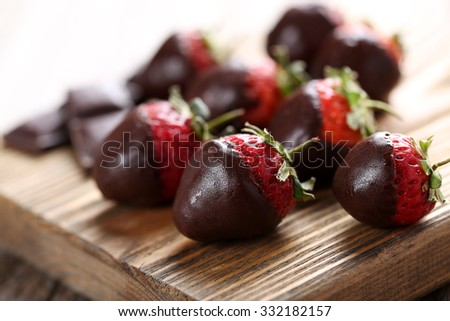 Fresh strawberries dipped in dark chocolate on grey wooden background - stock photo